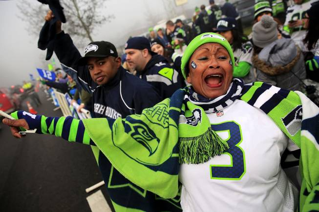 Marcia Shiri-Wasto, center, cheers with Seattle football fans on South 188th Street in SeaTac, Wash. Sunday, Jan. 26, 2014. The Seahawks drove past the crowd on route to the airport for Super Bowl XLVIII.