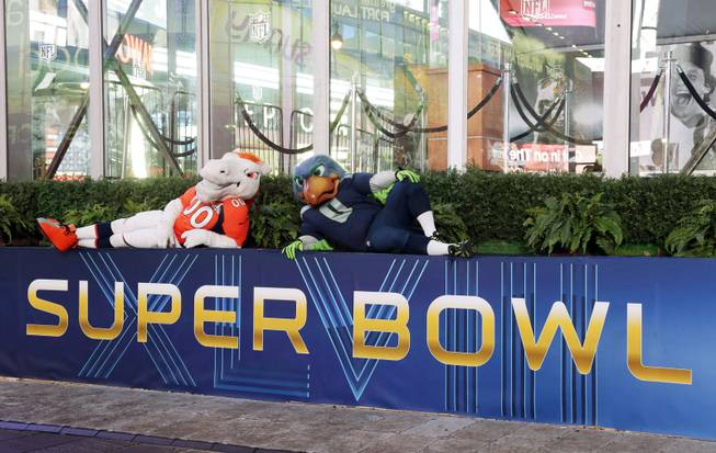 Blitz, right, the Seattle Seahawks mascot, is sits with Miles, left, the Denver Broncos mascot, Friday, Jan. 31, 2014 on top of a Super Bowl sign during a live broadcast of Good Morning America at Times Square in New York. The Seattle Seahawks will play the Broncos Sunday in the NFL Super Bowl XLVIII football game in East Rutherford, N.J.