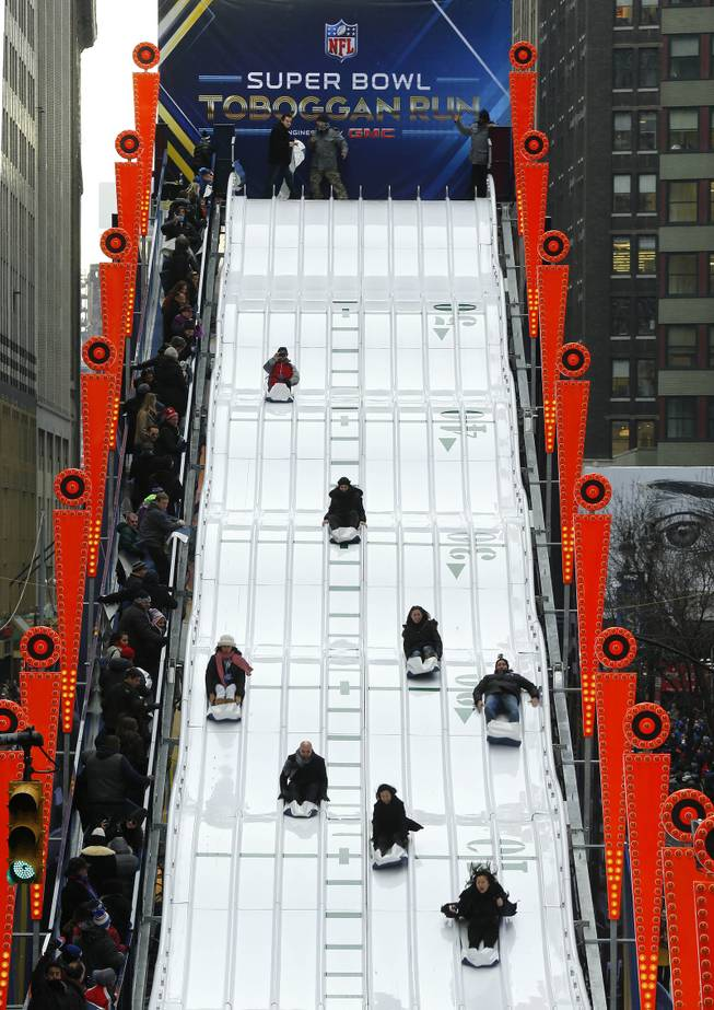 People ride the Super Bowl Toboggan Run along on Super Bowl Boulevard in New York on Friday, Jan. 31, 2014. The Seattle Seahawks play the Denver Broncos on Sunday at the stadium in the NFL Super Bowl XLVIII football game.