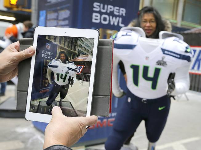 Tess DiMalanta, from the Philippines, poses for a photo in a Seattle Seahawks cut out along Super Bowl Boulevard Friday, Jan. 31, 2014, in New York. The Denver Broncos and Seahawks will face off Sunday in Super Bowl XLVIII in East Rutherford, NJ.