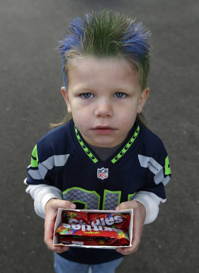 Seattle Seahawks fan Oskar Van De Plasch, 4, poses for a photo as he carries an offering of the Skittles candy favored by Seattle Seahawks running back Marshawn Lynch as he waits at the Seahawks' headquarters in Renton, Wash., Sunday, Jan. 26, 2014, to see players and coaches board buses for their flight to play the Denver Broncos in the NFL Super Bowl XLVIII football game in East Rutherford, N.J.