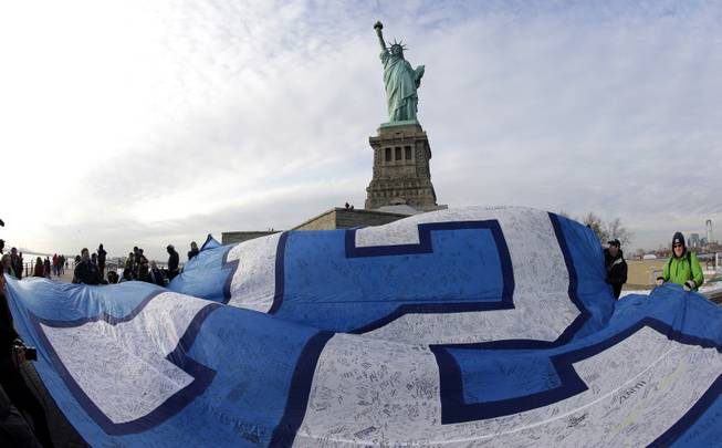 "A giant Seattle Seahawks ""12th Man"" flag that flew on the Space Needle before being signed by fans and brought to New York, is displayed at the Statue of Liberty, Friday, Jan. 31, 2014 in New York. The flag will be given to the Seahawks team as a gift from their fans before they play the Denver Broncos Sunday in the NFL Super Bowl XLVIII football game in East Rutherford, N.J."
