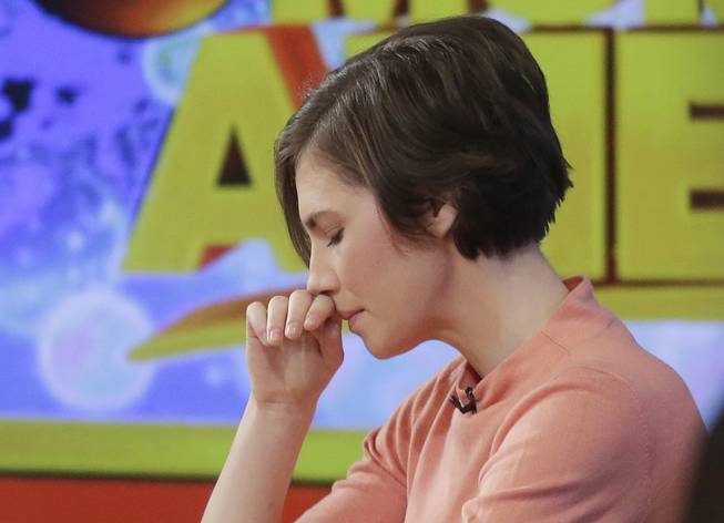 "Amanda Knox puts her hand to her face while making a television appearance, Friday, Jan. 31, 2014, in New York. Knox said she will fight the reinstated guilty verdict against her and an ex-boyfriend in the 2007 slaying of a British roommate in Italy and vowed to ""never go willingly"" to face her fate in that country's judicial system . ""I'm going to fight this to the very end,"" she said in an interview with Robin Roberts on ABC's ""Good Morning America."""