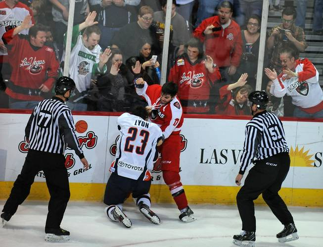Las Vegas fans cheer on Wranglers forward Adam Huxley (17) as he fights Ontario Reign forward Brett Lyon (23) during an ECHL game on Friday night at the Orleans Arena.