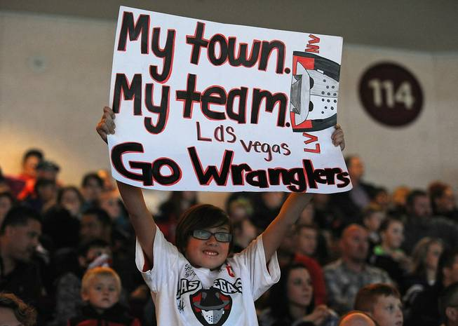 Las Vegas Wranglers fan Emily Adams, 10, holds up a sign she made in support of the home team as they faced off against the Ontario Reign on Friday night at the Orleans Arena.