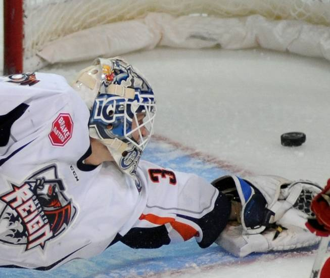 Ontario Reign goaltender Jussi Olkinuora reaches for a puck as it skitters into the net first period Wranglers goal on Friday night at the Orleans Arena.