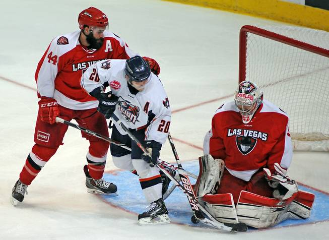 Las Vegas Wranglers goaltender Travis Fullerton makes a save against Ontario Reign forward Mario Lamoureux during the third period of a game on Saturday evening at the Orleans Arena. Wranglers defenseman Nolan Julseth-White is also pictured on the play.