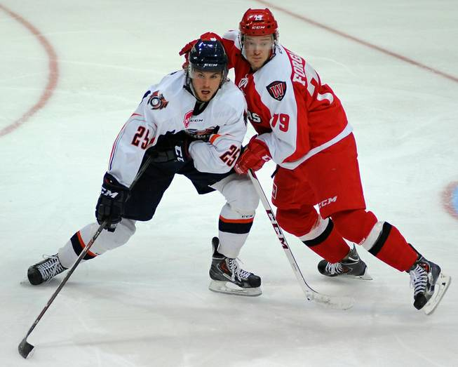 Las Vegas Wranglers defenseman Ryan Forgaard battles for position with Ontario Reign right winger Sebastian Stalberg during an ECHL game on Saturday night at the Orleans Arena.