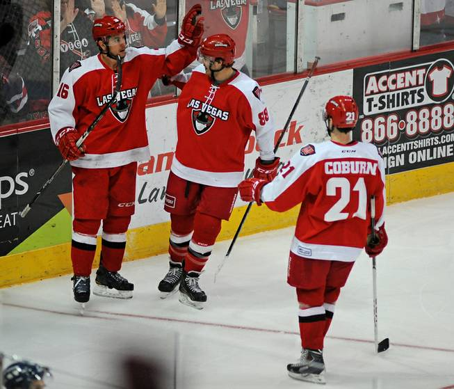 Wranglers forward Matt Tassone (16) is congratulated by teammates after scoring a late third period goal against the Ontario Reign on Saturday night.