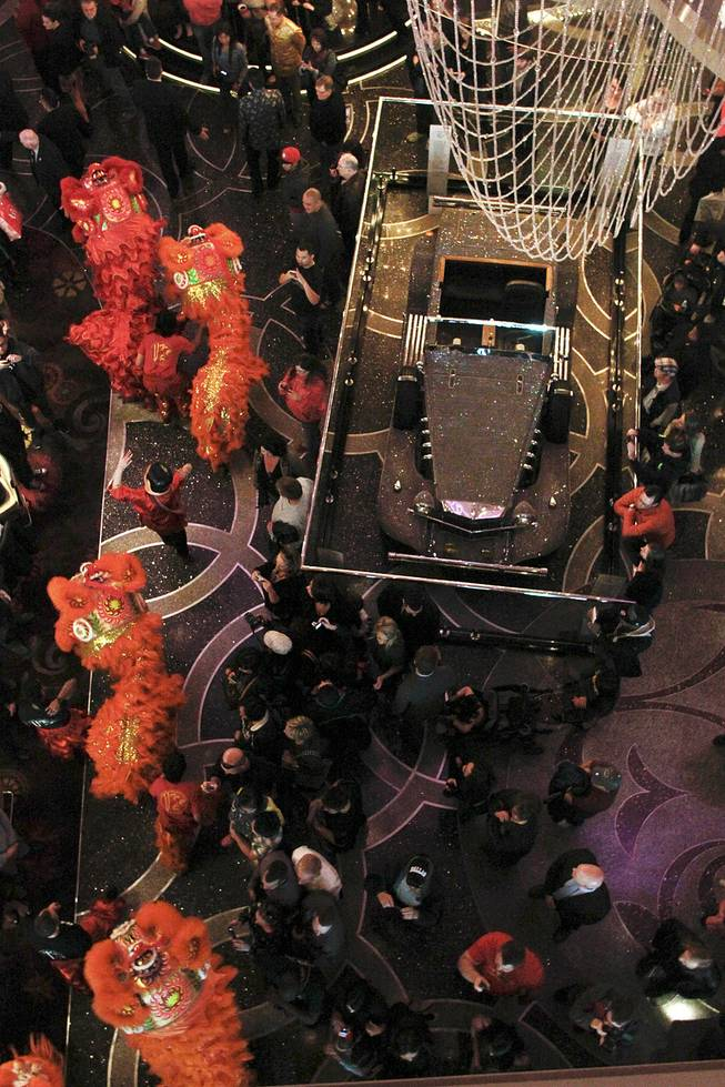 "Dancers make their way past a Liberace car on display during a ""Dotting of the Eyes"" ceremony as the Cosmopolitan marks the Year of the Horse Saturday, Feb. 1, 2014."