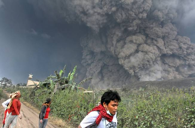 Villagers and a journalist prepare to flee as Mount Sinabung releases pyroclastic flows during an eruption in Namantaran, North Sumatra, Indonesia, on Saturday, Feb. 1, 2014. The rumbling volcano in western Indonesia has unleashed fresh clouds of searing gas, killing several people.