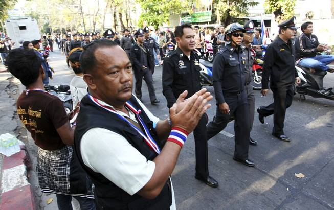 Anti-government protesters clap as Thai policemen walk in to take positions between pro- and anti-elections groups at Dindaeng district office in Bangkok, Thailand, on Sunday, Feb. 2, 2014. Thailand's tense national election got underway Sunday with protesters forcing the closure of several polling stations in the capital amid fears of more bloodshed a day after gun battles in Bangkok left seven people wounded.