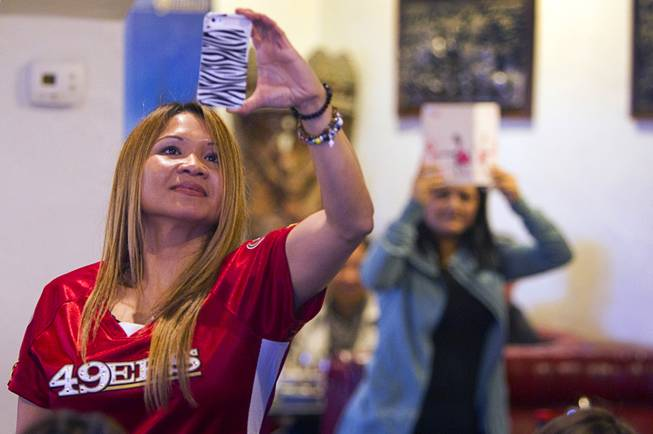 Phalenny Boswell takes a video with her phone during a lion dance at the Kung Fu Thai & Chinese Restaurant, 3505 S. Valley View Blvd. Sunday, Feb. 2, 2014. The traditional ceremony, performed by the Lohan School of Shaolin, was staged to drive out any evil spirits from the business.