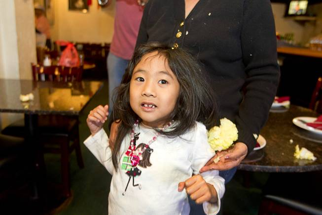 Evelyn Wong, 5, is covered in bits of lettuce after a lion dance at the Kung Fu Thai & Chinese Restaurant,3505 S. Valley View Blvd. Sunday, Feb. 2, 2014. The traditional ceremony, performed by the Lohan School of Shaolin, was staged to drive out any evil spirits from the business.