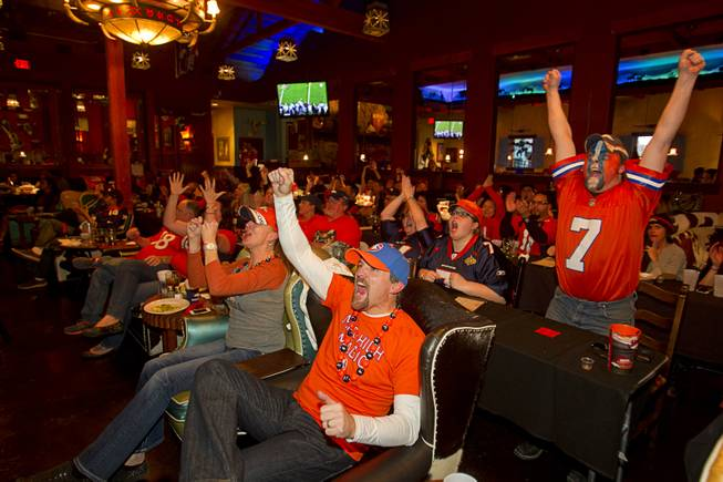 Denver fans Tim Frame, left, and Jason Platt, both originally from Colorado, cheer on the Broncos as they watch Super Bowl XLVIII from the Roadrunner Saloon, 9820 W. Flamingo Rd., Sunday, Feb. 2, 2014.
