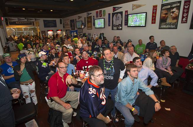 Seattle Seahawks fans are focused on a big screen as they watch Super Bowl XLVIII from a converted game area in Scooters Pub, 6200 S. Rainbow Blvd., Sunday, Feb. 2, 2014.