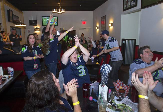 Fans cheer a play by the Seattle Seahawks as they watch Super Bowl XLVIII from Scooters Pub, 6200 S. Rainbow Blvd., Sunday, Feb. 2, 2014.