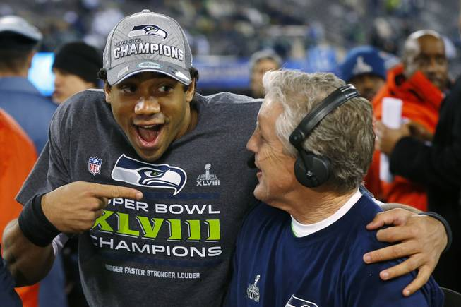 Seattle Seahawks quarterback Russell Wilson laughs with Seahawks head coach Pete Carroll during a TV interview after Super Bowl XLVIII on Sunday, Feb. 2, 2014, in East Rutherford, N.J. The Seahawks defeated the Denver Broncos 43-8.