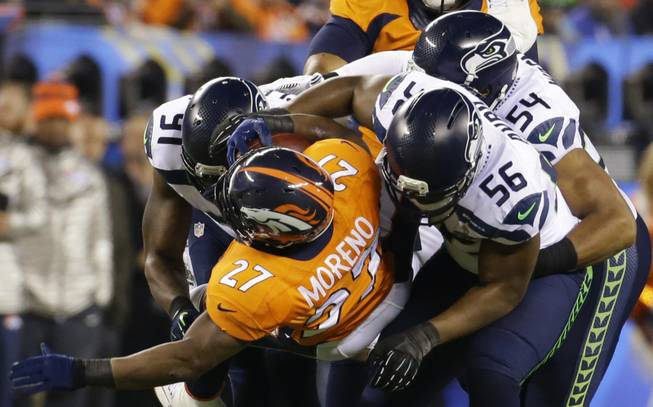 Denver Broncos' Knowshon Moreno (27) is tackled by Seattle Seahawks' Chris Clemons (91), Bobby Wagner and Cliff Avril (56) during the first half of the NFL Super Bowl XLVIII football game Sunday, Feb. 2, 2014, in East Rutherford, N.J. (AP Photo/Ted S. Warren)