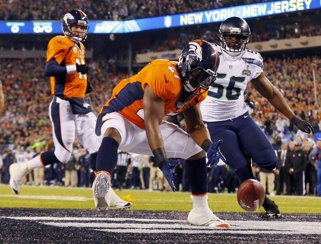 Denver Broncos' Knowshon Moreno reaches for a loose ball after the snap passed teammate Peyton Manning, left, during the first half of the NFL Super Bowl XLVIII football game Sunday, Feb. 2, 2014, in East Rutherford, N.J. Seattle Seahawks' Cliff Avril approached at right.