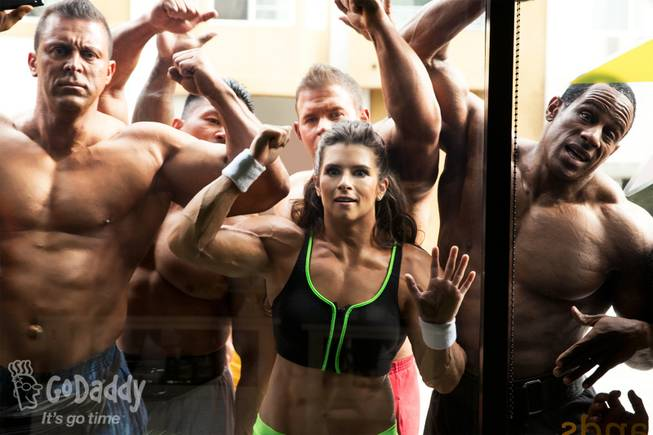 In this image released by GoDaddy.com on Wednesday, Jan. 22, 2014, NASCAR driver Danica Patrick, in a muscle suit, appears with bodybuilders in a Super Bowl XLVIII ad shot in Long Beach, Calif. The ad is expected to air after halftime.