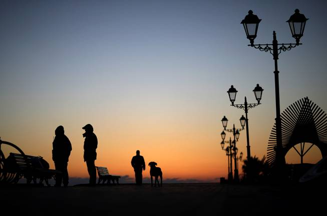 Police patrol along the boardwalk on the Black Sea accompanied by a stray dog outside the Olympic Park at the 2014 Winter Olympics, Monday, Feb. 3, 2014, in Sochi, Russia.