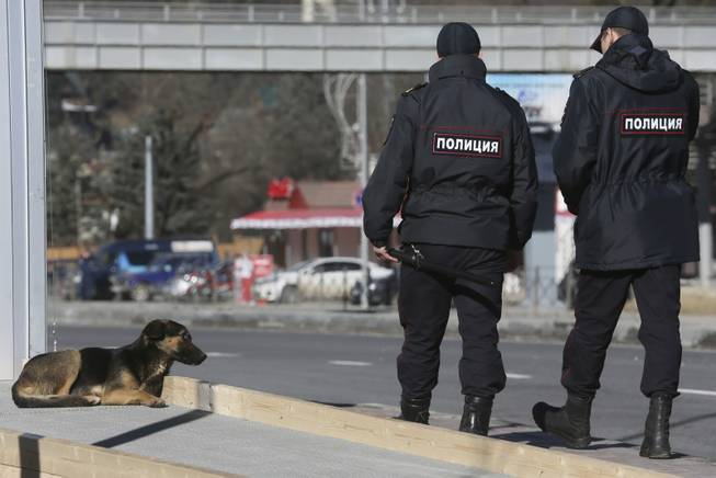 Policemen walk past a stray dog near the Media Center of the 2014 Winter Olympics, Monday, Feb. 3, 2014, in Krasnaya Polyana, Russia.
