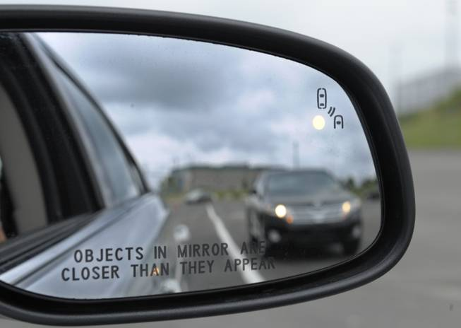 This May 22, 2012, file photo shows a side mirror warning signal in a Ford Taurus at an automobile testing area in Oxon Hill, Md. Federal officials want automakers to equip new cars and light trucks with technology that enables vehicles to communicate with each other to prevent collisions.