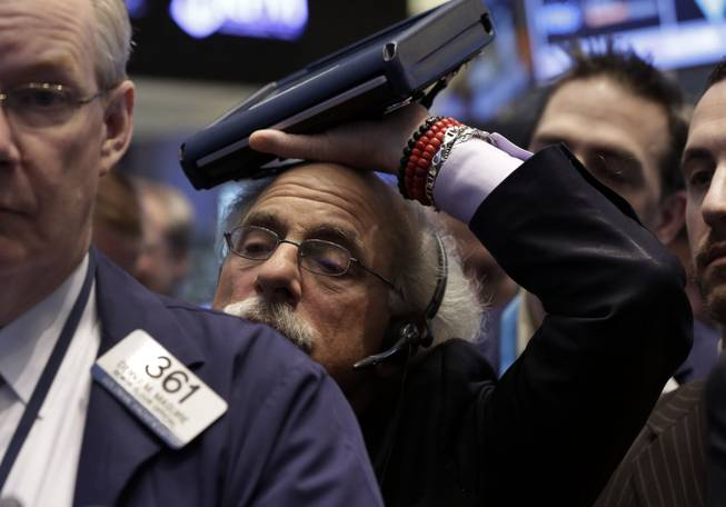 Trader Peter Tuchman rests his handheld device on his head as he works on the floor of the New York Stock Exchange Friday, Jan. 31, 2014.
