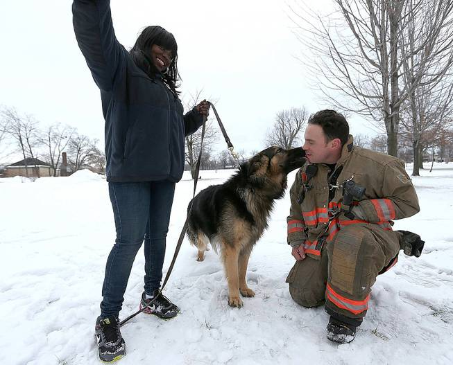 Rescue 1 firefighter Michael Paveljack gets a kiss from Mack the dog he rescued from a sinkhole in Buffalo, N.Y., on Sunday, Feb. 2, 2014.
