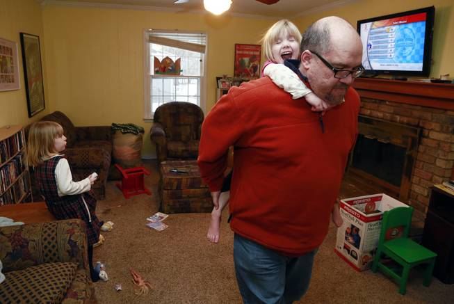 Mike Beck carries his daughter Veronica on his back through the family's living room as his daughter Maria, left, plays a video while trying to combat cabin fever, Monday, Feb. 3, 2014, in Indianapolis.