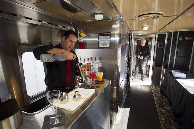 Eddie Ybarra, an event captain with Masterpiece Cuisine, mixes drinks during a tour of X Train Club cars Tuesday, Feb. 4, 2014.