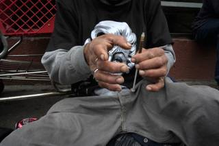 A drug addict prepares a needle to inject himself with heroin in front of a church in the Skid Row area of Los Angeles, Monday, May 6, 2013. It's not a rare scene on Skid Row to spot addicts using drugs in the open, even when police patrol the area.