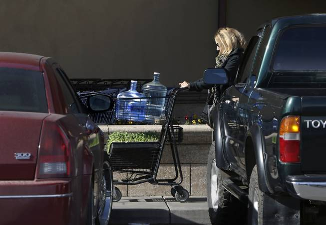 In this photo taken Tuesday, Feb. 4, 2014,  Kathleen Camp leaves a local market with bottled water in Willits, Calif.  With area reservoirs holding less than a 100-day supply of water, city leaders have banned lawn watering, car washing and mandated all residents to cut water use.
