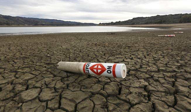 In this Tuesday, Feb. 4, 2014, photo, a warning buoy sits on the dry, cracked bed of Lake Mendocino near Ukiah, Calif. Despite recent spot rains, the reservoir is currently only about 37 percent full. California is amid a historic drought, prompting Gov. Jerry Brown to declare a state of emergency.