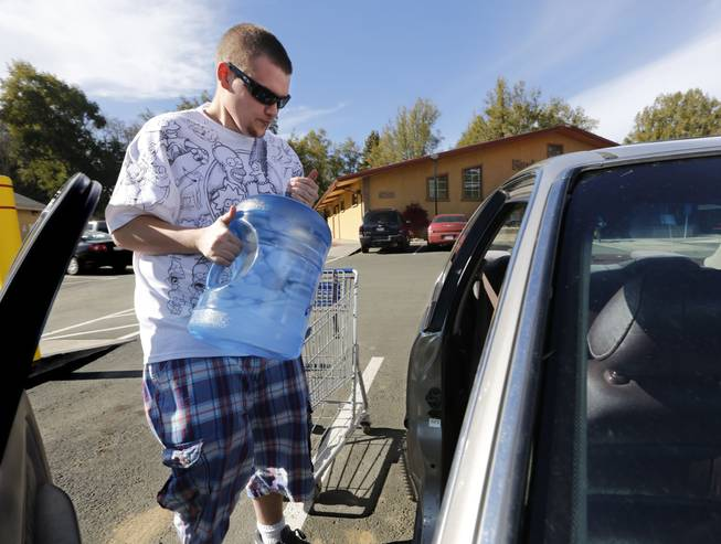 In this photo taken Tuesday, Feb. 4, 2014, Forrest Clark, 25, loads five gallon bottles of water, purchased at a local store, into his car in Willits, Calif.  With local reservoirs holding less than a 100-day supply of water, city leaders have banned lawn watering, car washing and mandated all residents to cut water use. Clark, who said he doesn't like the taste of the local water, buys 10-15 gallons of bottled water a week to help boost the family water supply.