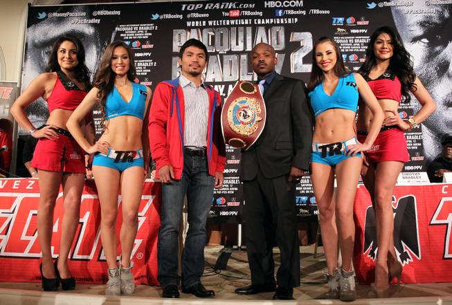 Feb.  4, 2014, Beverly Hills ,Ca.   ---  (L-R)  Manny Pacquiao and undefeated WBO World Welterweight  champion Timothy Bradley(surrounded by the Top Rank Knockouts and Tecate Girls)  pose during the press conference  in Beverly Hills to announce their upcoming rematch during a two-city media tour in Los Angeles on Tuesday and New York on Thursday.  Pacquiao vs. Bradley 2 will take place, Saturday, April 12 at the MGM Grand Garden Arena in Las Vegas. Chris Farina - Top Rank