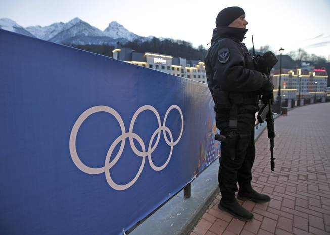 An armed Russian security guard stands at the ski resort Rosa Khutor, where the snow and sliding sports venues for the 2014 Winter Olympics are located, Tuesday, Feb. 4, 2014, in Krasnaya Polyana, Russia.