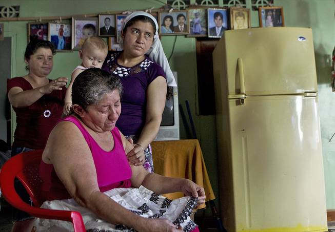 Maria Alvarenga, the mother of Jose Salvador Alvarenga, is comforted by relatives during an interview inside her home in the village of Garita Palmera, El Salvador, Tuesday, Feb. 4, 2014.