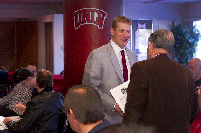 UNLV head football coach Bobby Hauck talks with former regent Mark Alden before a news conference on new recruits at UNLV Wednesday, Feb. 5, 2014.