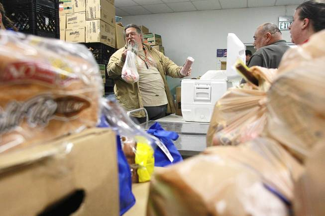 Volunteer Shane Smith pulls frozen items to add to a box of food at Our Savior Church's food line Wednesday, Feb. 5, 2014 in Henderson.