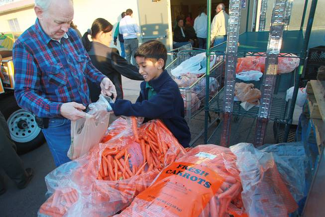 Volunteers Steve Wildman, left, and Luke Mathews portion our bags of carrots to be given away at Our Savior Church's food line Wednesday, Feb. 5, 2014 in Henderson.