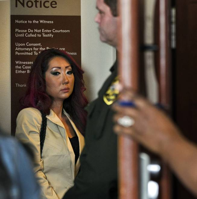 Gloria Lee, accused of arson and animal cruelty in connection with a fire at her pet store, Prince and Princess Pet Boutique, awaits her escort to leave the courtroom  Wednesday, Feb. 5, 2014.
