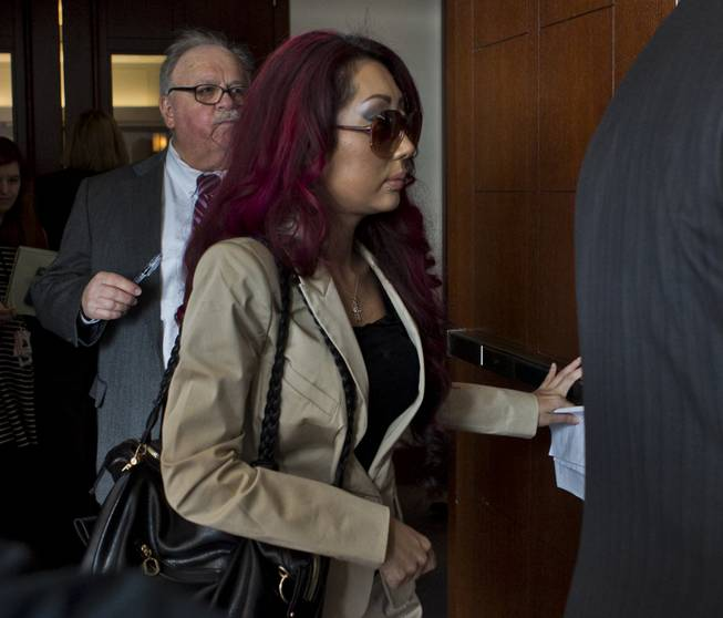 Gloria Lee, accused of arson and animal cruelty, in connection with a fire at her pet store, Prince and Princess Pet Boutique, is escorted from the courtroom Wednesday, Feb. 5, 2014.