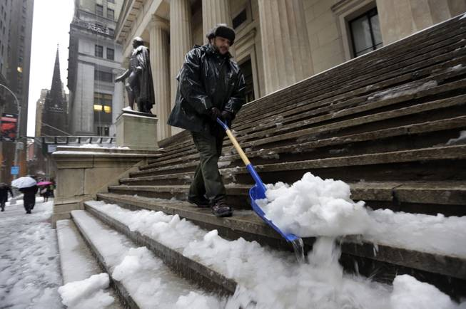 U.S. Parks Service employee Danny Merced clears snow from the steps of Federal Hall, in New York's Financial District, Wednesday, Feb. 5, 2014.  New York City's sanitation commissioner says some secondary streets still need plowing but overall snow removal was going well. Around 6 inches of snow are expected in parts of the metropolitan area on Wednesday.