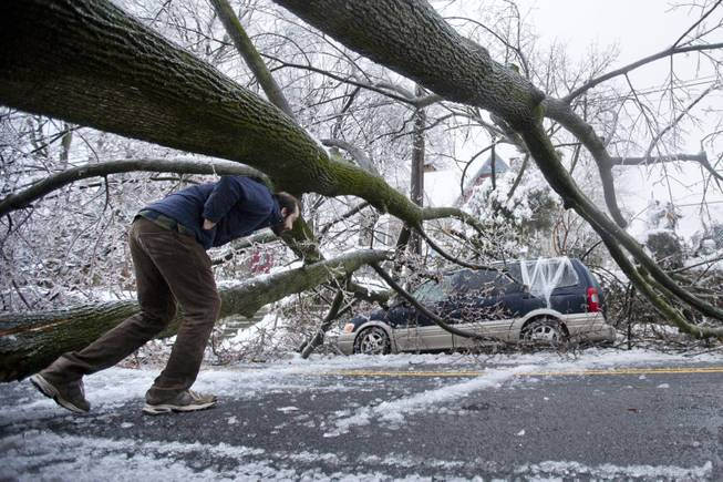 A man inspects an ice covered downed tree that took out an utility line and landed atop a minivan, after a winter storm Wednesday, Feb. 5, 2014, in Philadelphia. Icy conditions have knocked out power to more than 200,000 electric customers in southeastern Pennsylvania and prompted school and legislative delays as well as speed reductions on major roadways.