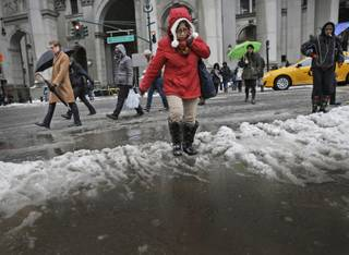Pedestrians make their way through a slushand water at an intersection in New York, Wednesday, Feb. 5, 2014. Around 6 inches of snow are expected in parts of the metropolitan area on Wednesday.