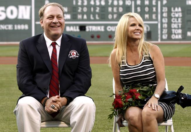 Former Boston Red Sox pitcher Curt Schilling sits with his wife, Shonda, right, after being introduced as a new member of the Boston Red Sox Hall of Fame before a baseball game between the Boston Red Sox and the Minnesota Twins at Fenway Park in Boston, Friday, Aug. 3, 2012.