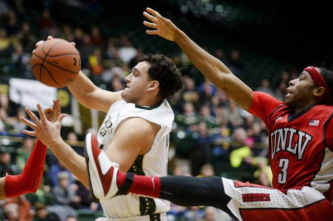 Colorado State's J.J. Avila, center, and UNLV's Kevin Olekaibe come down from the basket during the second half of an NCAA college basketball game Wednesday, Feb. 5, 2014, at Moby Arena in Fort Collins, Colo. Colorado State won 75-57.