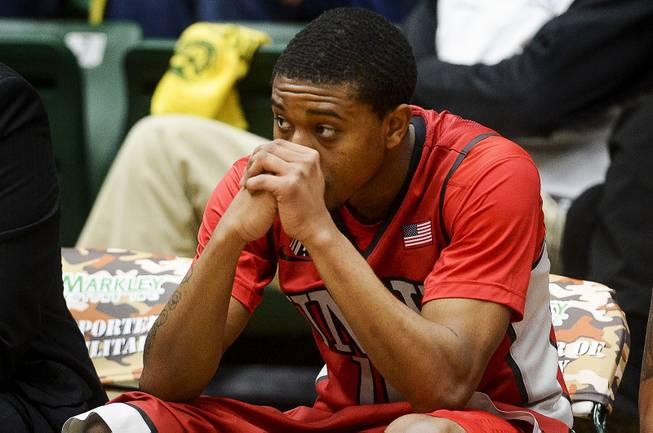 UNLV's Daquan Cook sits on the bench as he watches his team during a 75-57 loss to Colorado State in an NCAA college basketball game Wednesday, Feb. 5, 2014, at Moby Arena in Fort Collins, Colo.
